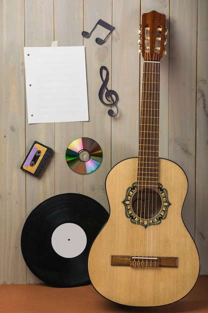 Blank musical page; cassette; compact disc; and musical note stuck on wooden wall with guitar and vinyl record Free Photo