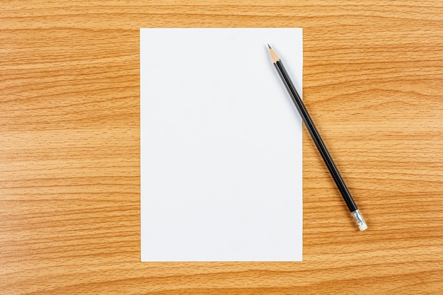 Blank note paper and a pencil on wooden desk. - blank space for advertising text. Premium Photo