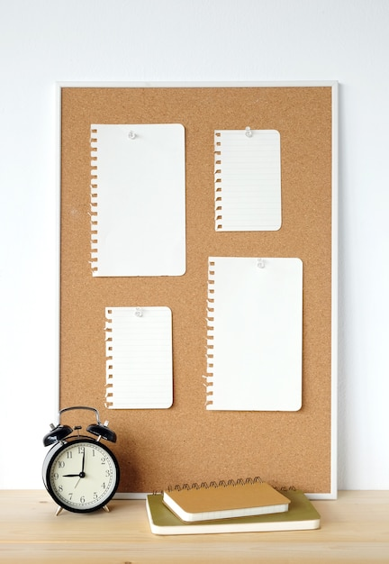 Blank note papers on cork board and clock on wood table Premium Photo