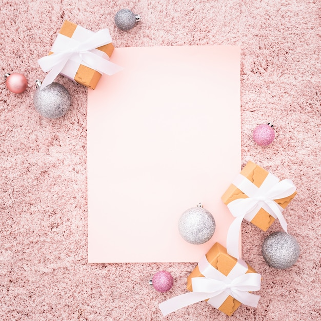 Blank note with christmas ornaments on a pink textured carpet Free Photo