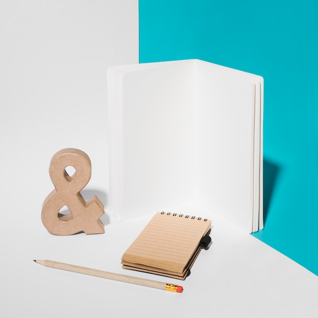 Blank notebook; ampersand symbol; pencil; and spiral notepad on background Free Photo