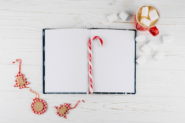 Blank notebook with candy cane on table Free Photo