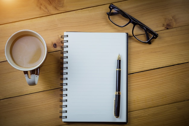 Blank notebook with pen and with glasses next to cup of coffee on wooden table Premium Photo