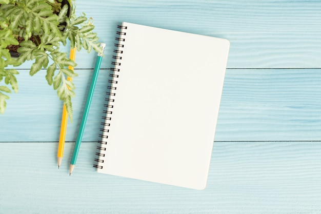 Blank notebook with and pencil on blue background Premium Photo