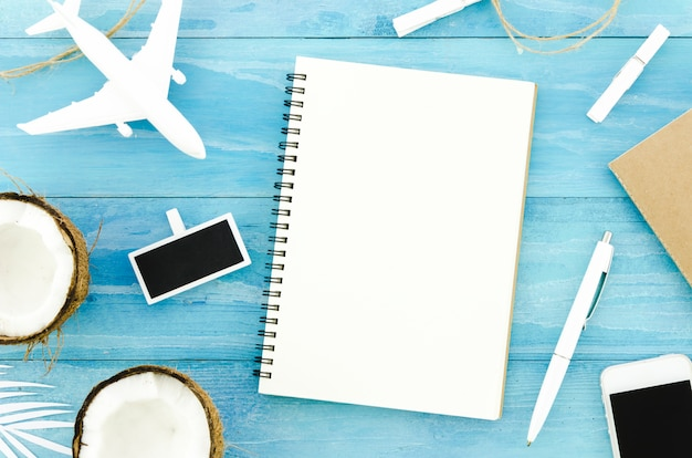Blank notebook with toy plane and coconuts Free Photo