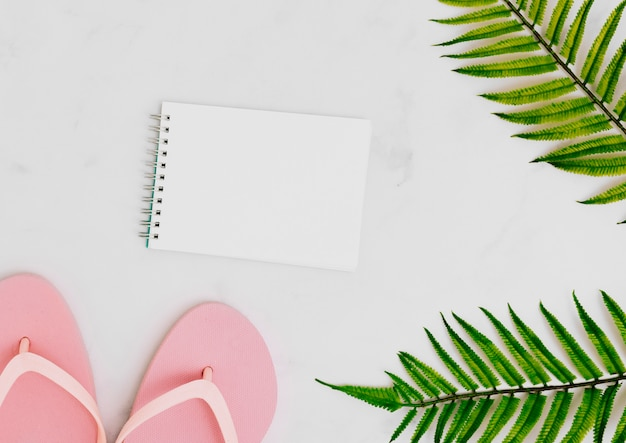 Blank notebook with tropical palm leaf Free Photo