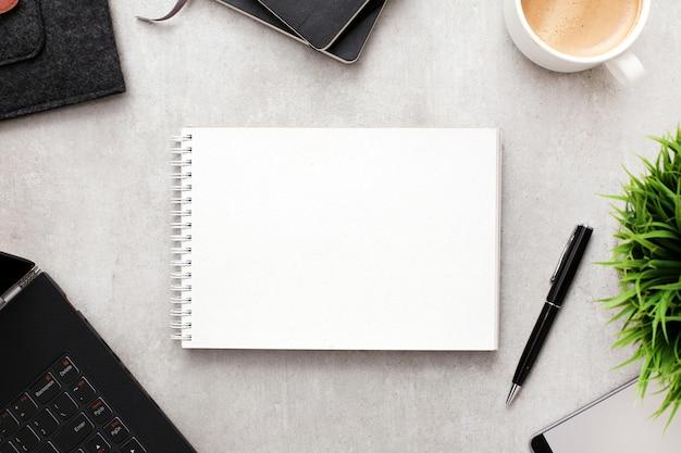Blocco note o taccuino in bianco su area di lavoro con gli articoli per ufficio, vista superiore Foto Gratuite