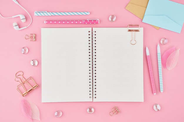 Blank notepad page in bullet journal on bright pink office desktop. top view of modern bright table Premium Photo