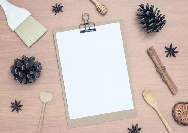 木製のテーブルの背景に松のコーンと空白のメモ帳 Premium写真