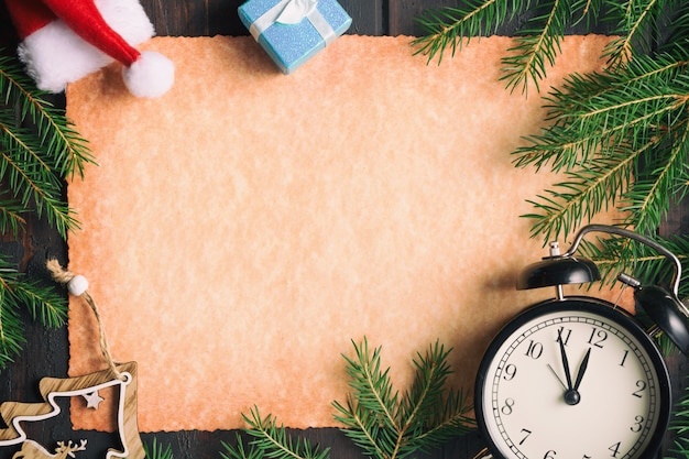Blank old paper with christmas fir tree branches with vintage alarm clock, gift boxes and santa hat. Premium Photo