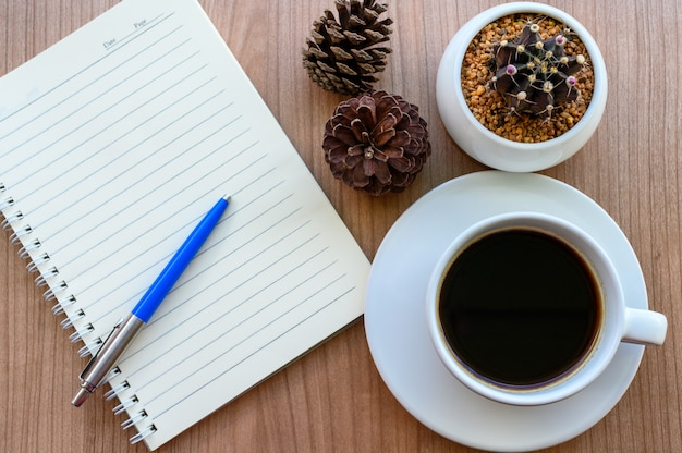 Blank page of note book with black coffee cup, cactus, pine cones on wooden table, flat lay Premium Photo