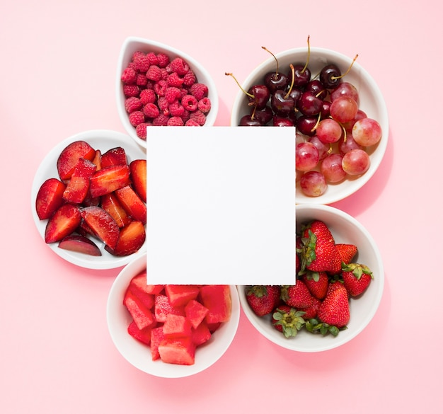 Blank page over the raspberries; plums; watermelon; strawberries; cherries; grapes and strawberries on pink background Free Photo
