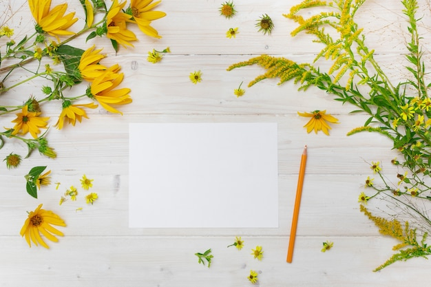 A blank paper beside a yellow pencil on a wooden surface with yellow-petaled flowers Free Photo