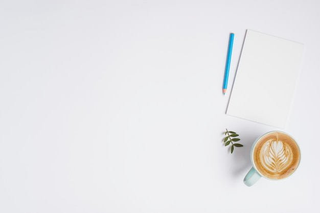 Blank paper; blue colored pencil and cup of cappuccino coffee on white background Free Photo