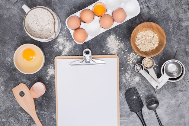 Blank paper on clipboard with baking ingredients over concrete backdrop Free Photo