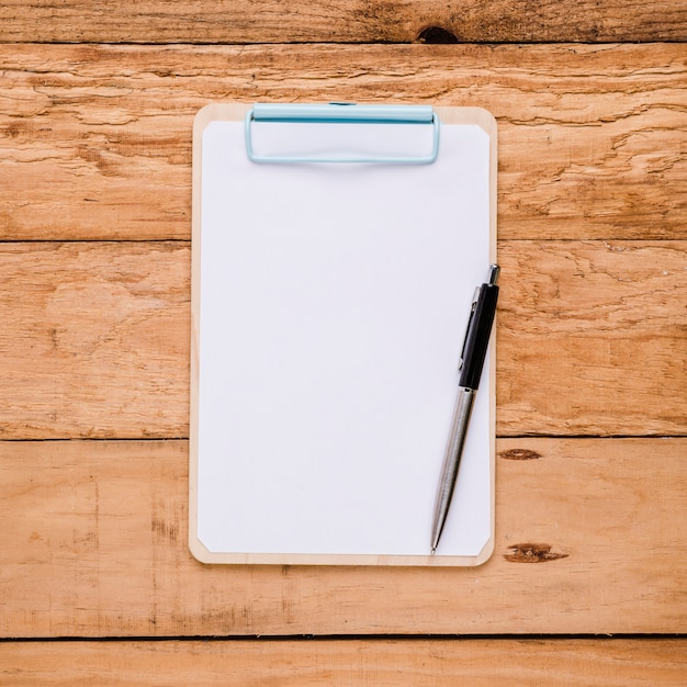 Blank paper on clipboard with ballpoint pen over wooden desk Free Photo