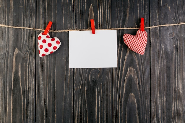 Blank paper hanging between hearts on rope Free Photo