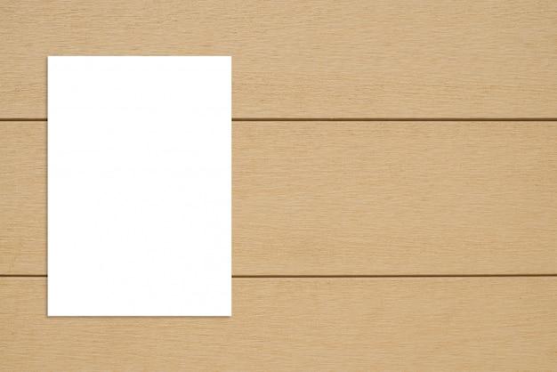 木製の壁に掛かっている空白の紙ポスター。 Premium写真