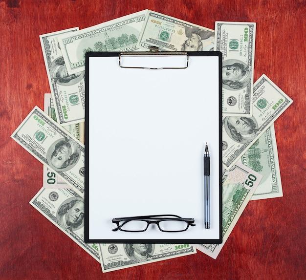 클립 보드에 빈 종이 시트는 돈 달러와 나무 배경의 중심에 배치 프리미엄 사진