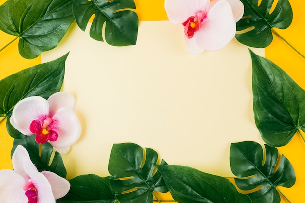 Blank paper surrounded with artificial leaves and orchid flowers on yellow background Free Photo