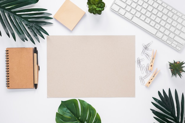 Blank paper surrounded with office supplies on white workspace Free Photo