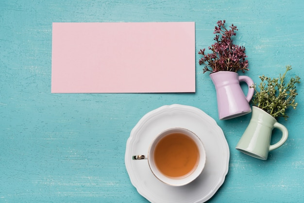 Blank paper and vases with cup of tea on blue textured background Free Photo