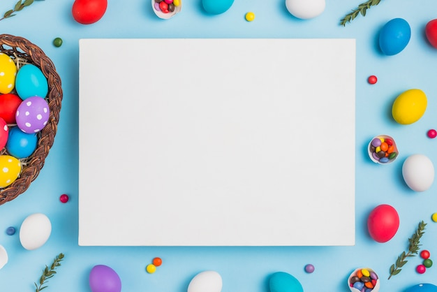 Blank paper with easter eggs in basket on table Free Photo