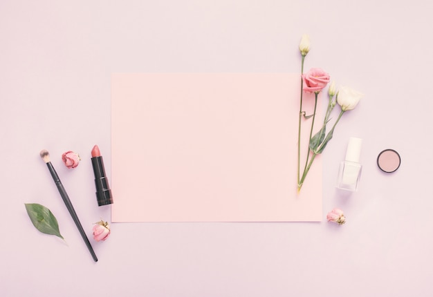 Blank paper with flowers, nail polish and lipstick on table Free Photo