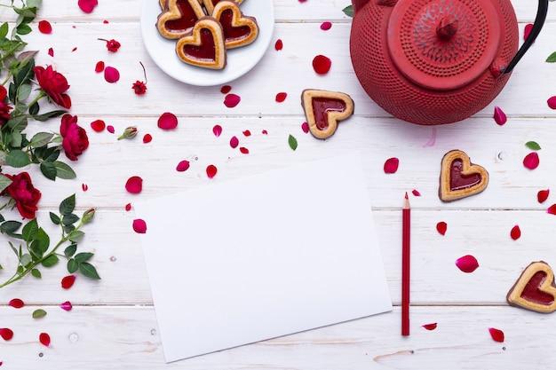 赤いティーポットとハート型のクッキーの近くの白い表面に赤いバラの花びらと白紙 無料写真