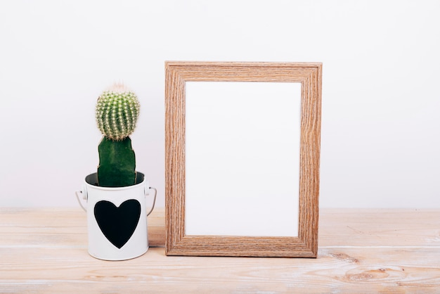 Blank photo frame and succulent plant with heartshape on pot over wooden table Free Photo