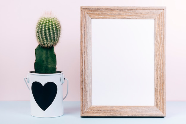 Blank photo frame and succulent plant with heartshape on pot Free Photo
