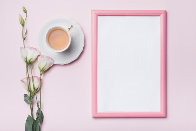Blank photo frame with pink border; cup of tea and fresh eustoma flowers against colored background Free Photo