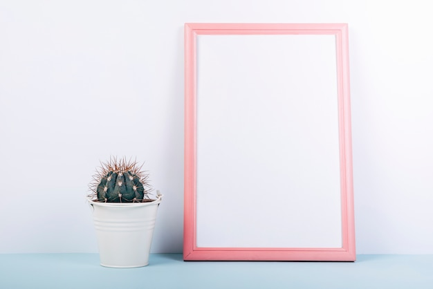 Blank photo frame with small succulent potted plant on blue table Free Photo