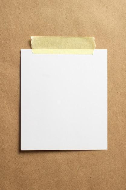 Пустая рамка для фотографий с мягкими тенями и желтой скотчем на фоне крафт-бумаги Бесплатные Фотографии