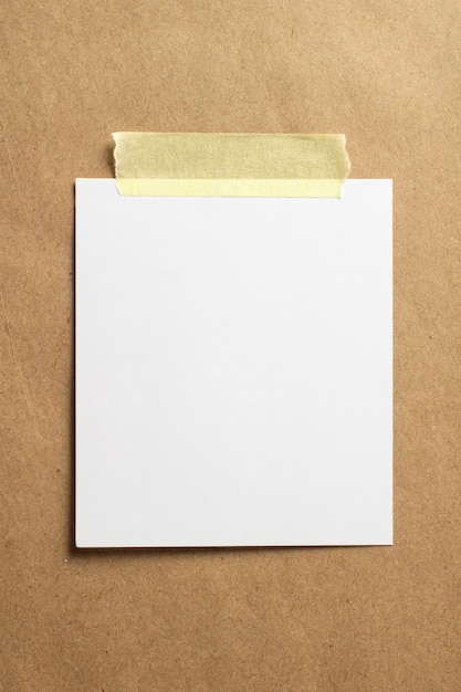 Blank photo frame with soft shadows and yellow scotch tape on craft cardboard paper background Free Photo