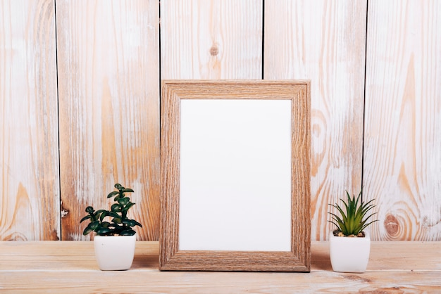 Blank photo frame with two succulent plants besides over wooden table Free Photo