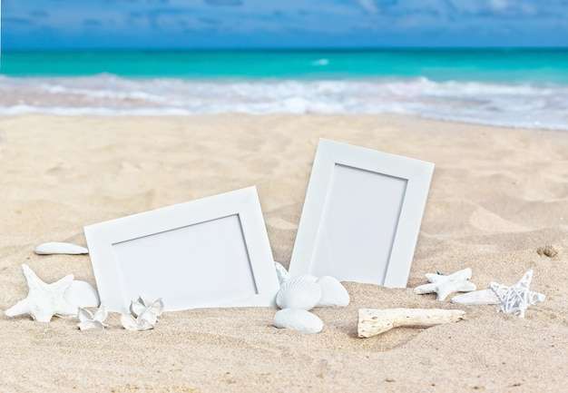 Blank photo frames on the sand beach with shells, starfish and candle. Premium Photo