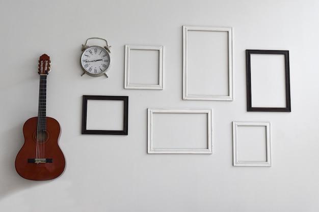 Пустые рамы для картин, часы и гитара на белой цементной стене. Premium Фотографии