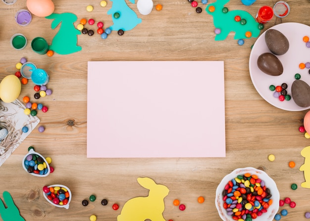 Blank pink paper surrounded with chocolates; easter bunny and gems candies on desk Free Photo