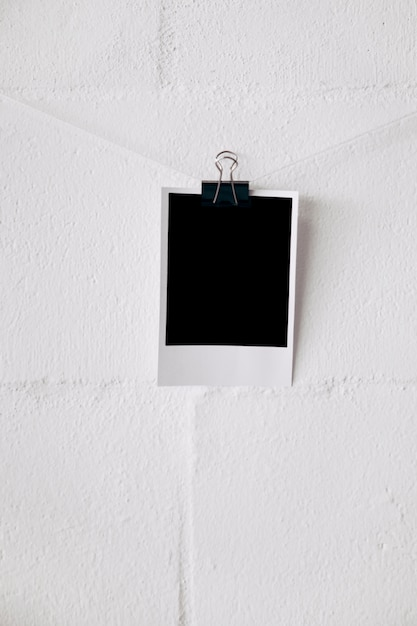 Blank polaroid photo on string attach with bulldog paper clips against white wall Free Photo
