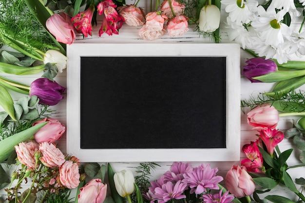 Blank rectangular slate surrounded with rose; tulip; chamomile and alstroemeria flowers Free Photo