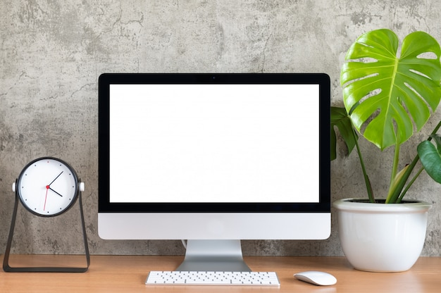 Blank screen of all in one computer, keyboard, mouse, monstera plant pot and clock  on wooden table Premium Photo