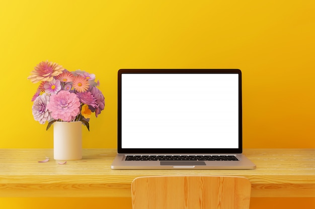 Blank screen computer placed on a wooden table with trees and headphones in a yellow room Premium Photo