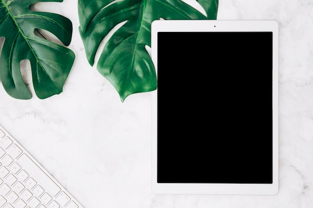 Blank screen digital tablet with monstera leaves and keyboard on white marble desk Free Photo