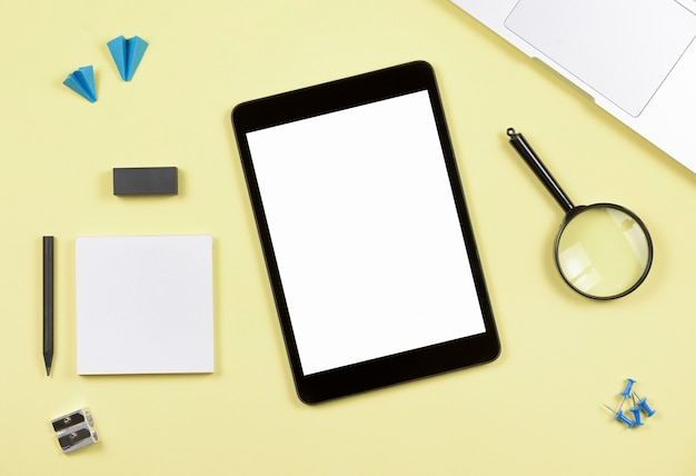 Blank screen digital tablet with office supplies on yellow backdrop Free Photo