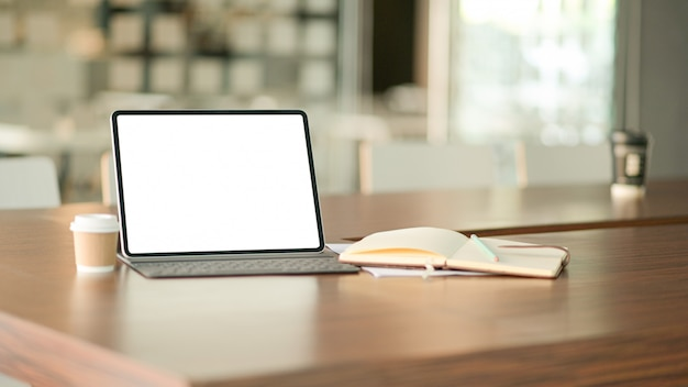 Blank screen laptop computer and a coffee in modern office with notebook. Premium Photo