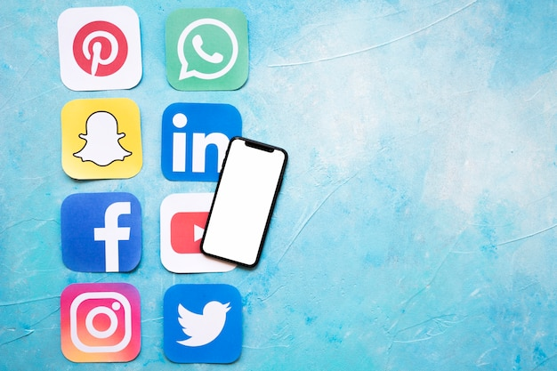 Blank screen mobile phone with media application icons over blue textured paint Free Photo