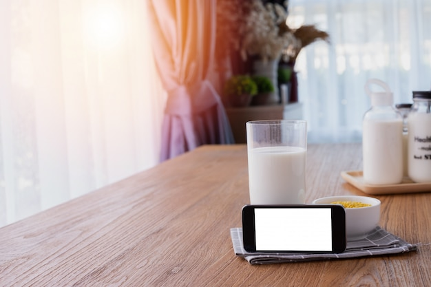 Blank screen on smart phone, tablet, cell phone with glass of milk on wood table. Premium Photo