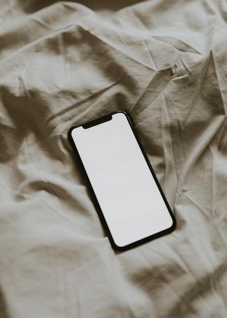 テクスチャード加工されたファブリック上の空白の画面のスマートフォン 無料写真