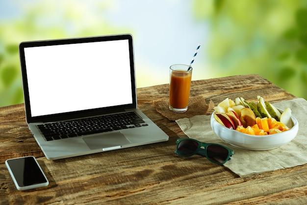 Schermi vuoti di laptop e smartphone su un tavolo di legno all'aperto con la natura sul muro frutta e succhi di frutta freschi nelle vicinanze. concetto di lavoro creativo, affari, freelance. copyspace. Foto Gratuite